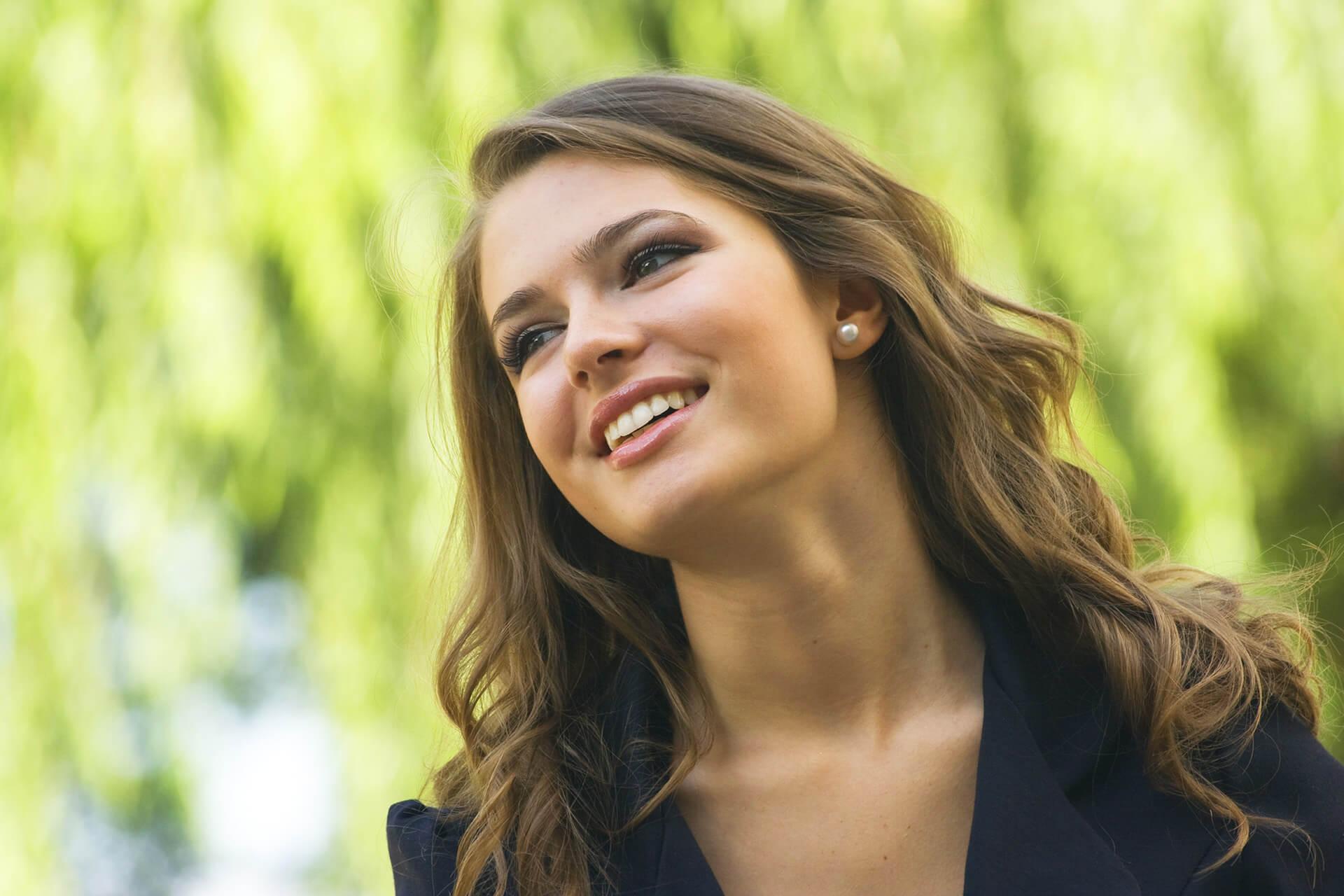 Huebsche Frau mit langen Haaren und schoenen Zaehnen laechelt vor hellgruenem Hintergrund