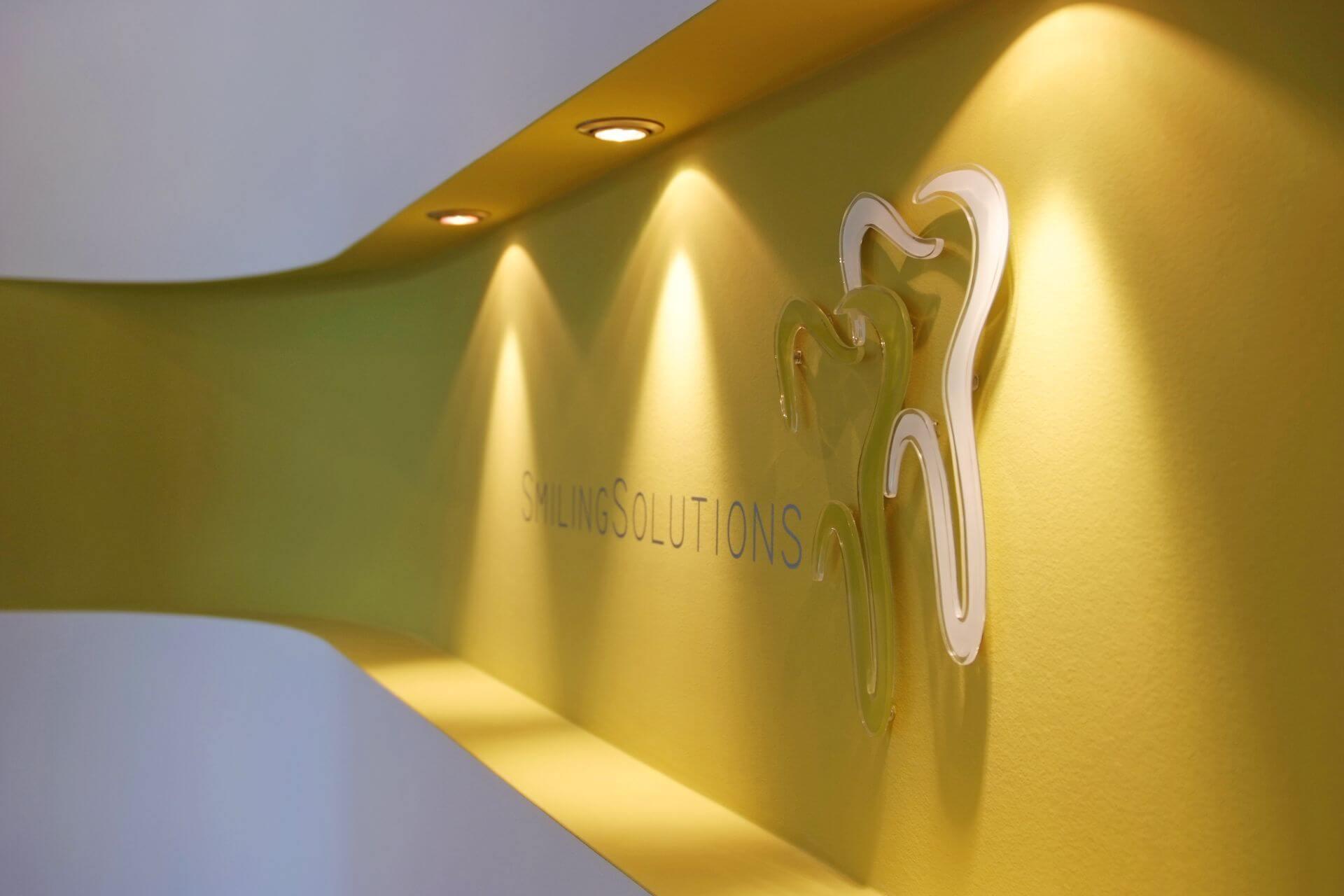 Smiling Solutions Logo am Empfang unserer Zahnarztpraxis