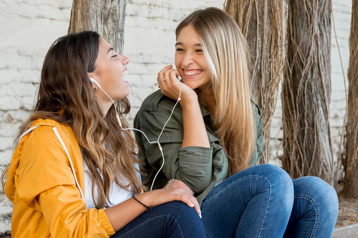 Zwei huebsche Maedels lachen mit schoenen Zaehnen