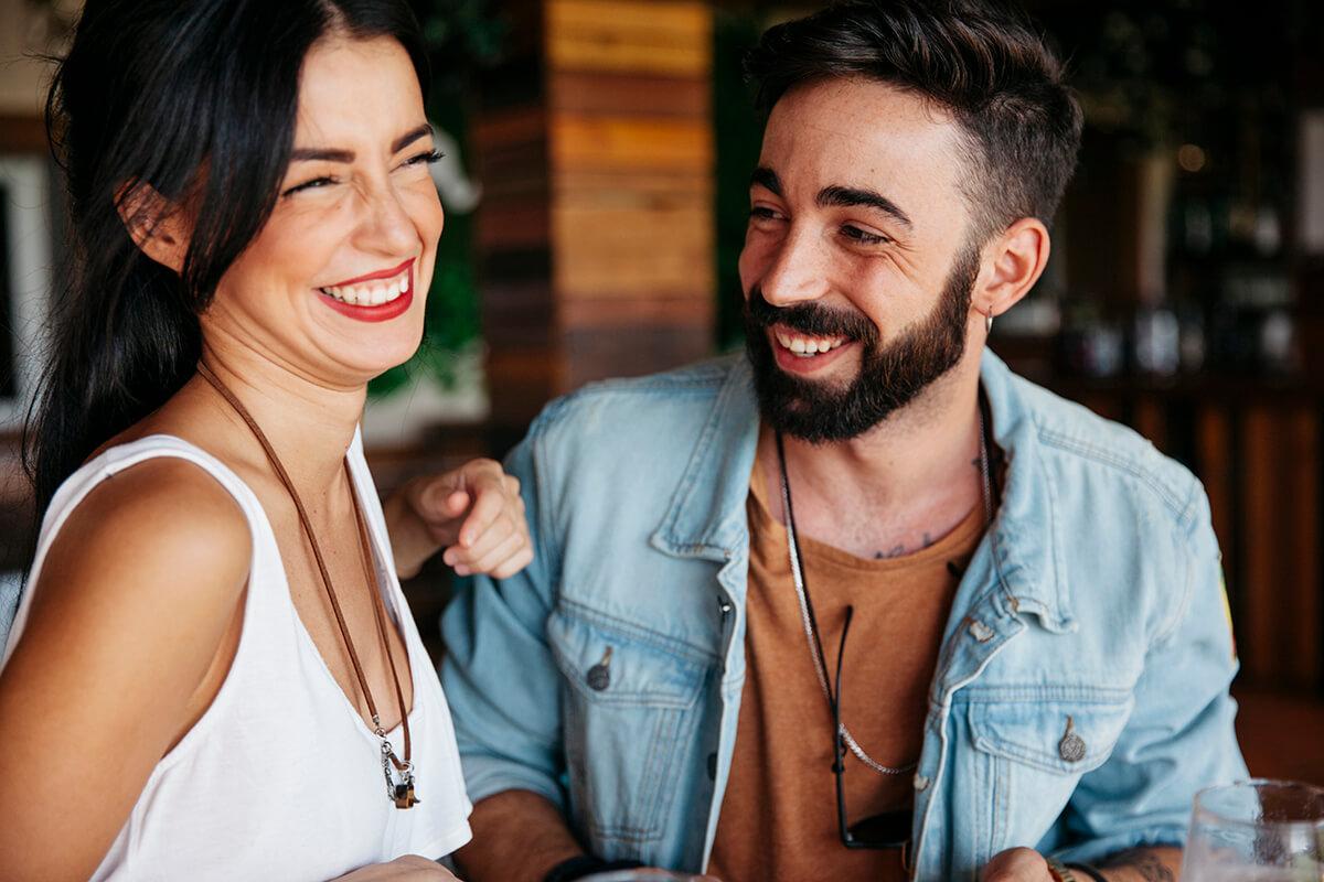 Paar mit weißen Zaehnen lacht sich an