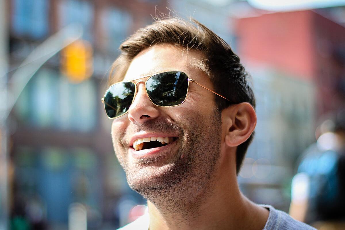 Lachender Mann mit Sonnenbrille und schoenen Zaehnen