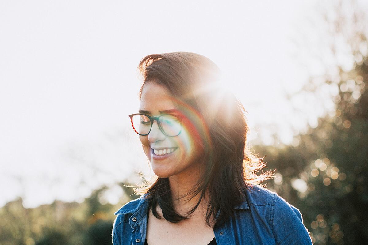 Lachende Frau mit Brille im Sonnenlicht