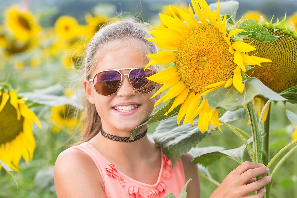Lachendes Kind mit Sonnenbrille und Sonnenblume