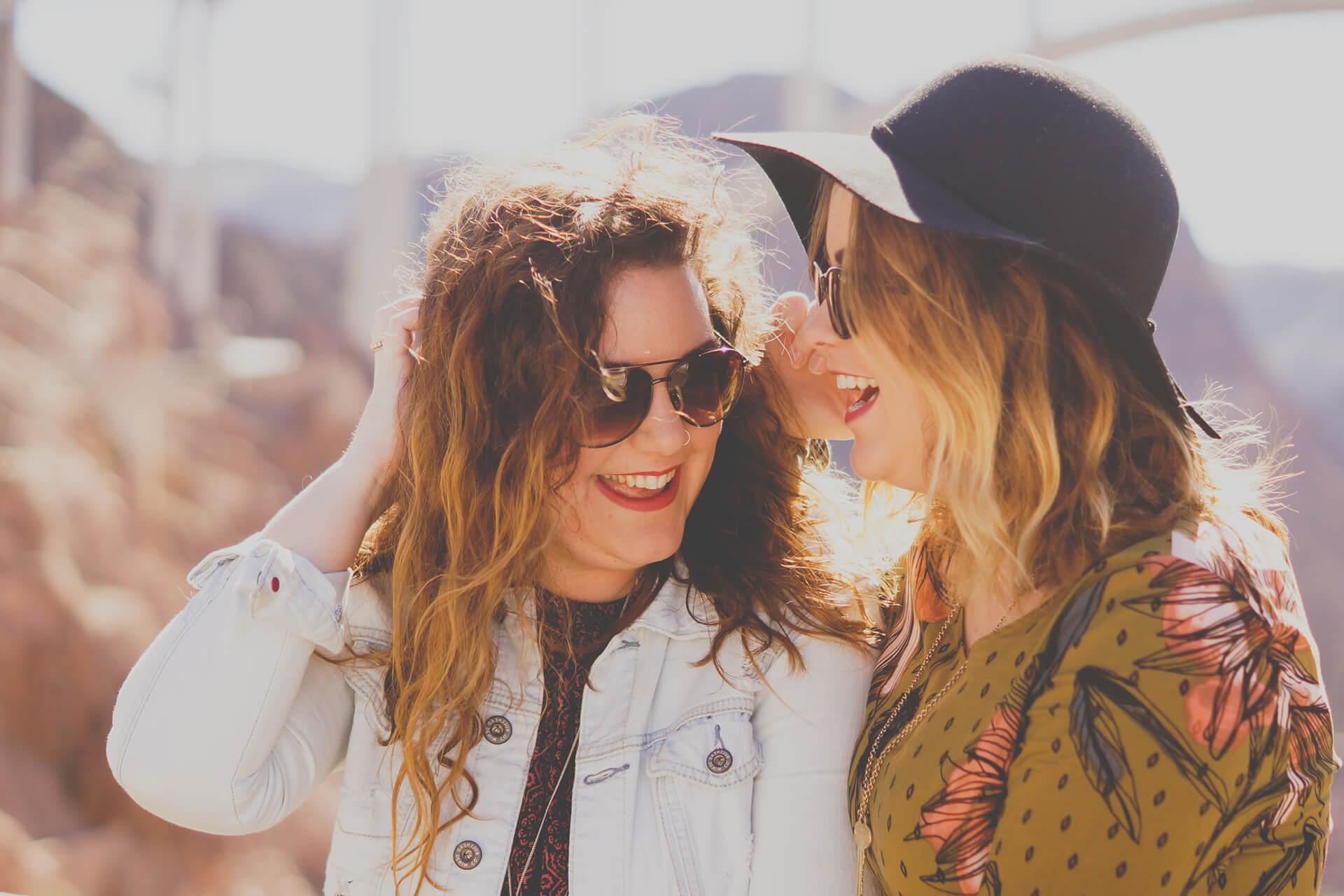 Zwei Freundinnen lachen in der Sonne mit schoenen Zaehnen