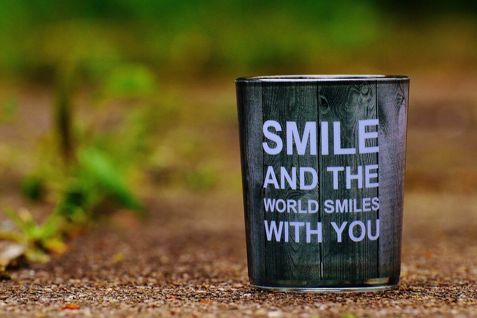 Becher vor Hintergrund mit Zitat SMILE AND THE WORLD SMILES WITH YOU